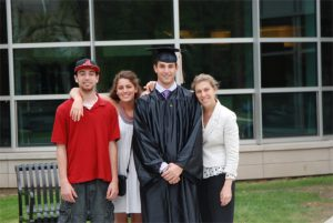 Family with college student in graduation cap and gown